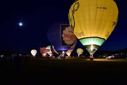 Hot air balloon preparation inflation start night glow