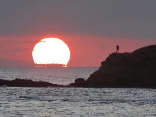 silhouette sunset ocean island alone
