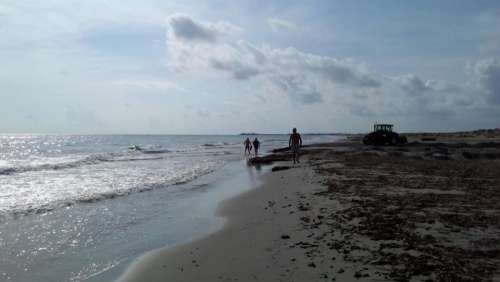 family walk beach clouds waves