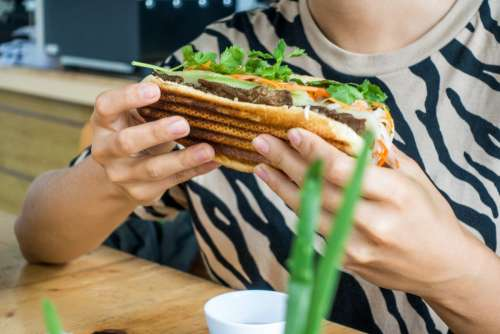 Girl eating fresh Vietnamese baguette banh mi
