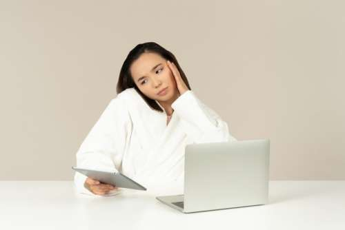 Bothered Young Asian Woman Talking On The Phone, Holding Tablet And Doing Online Shopping