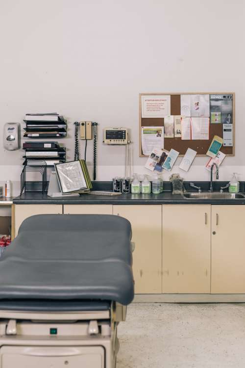 Empty Medical Examining Table Sitting Next To Supplies Photo