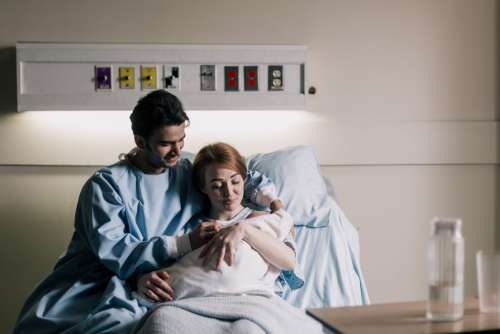 Mother And Father Sitting In Hospital Bed Admiring Newborn Photo