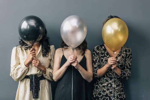 Party Balloons In front Of Faces Photo