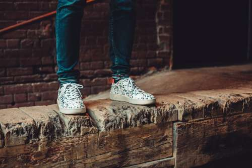 White Patterned Sneakers On Wooden Wall Photo