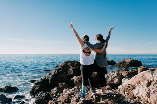 Women Arm In Arm Raise Their Hands In Peace Sign On Beach Photo