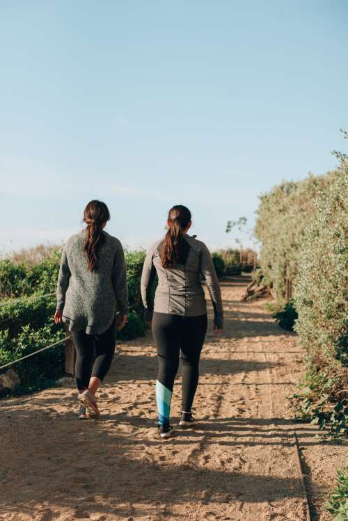 Women In Activewear Hike Up Sandy California Coastline Path Photo