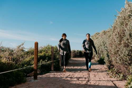 Women In Activewear Take A Beachside Hike On A Sandy Path Photo