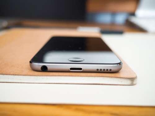 Phone and Sketchbook on Wooden Desk
