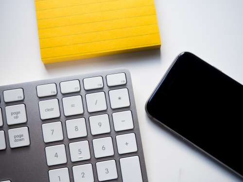 Keyboard, Phone, and Yellow Note on White Desk