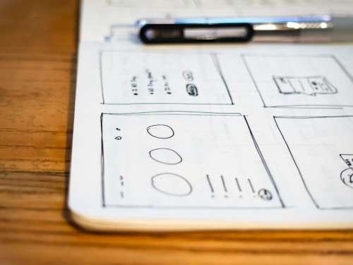Sketchbook and Pen on Wood Desk