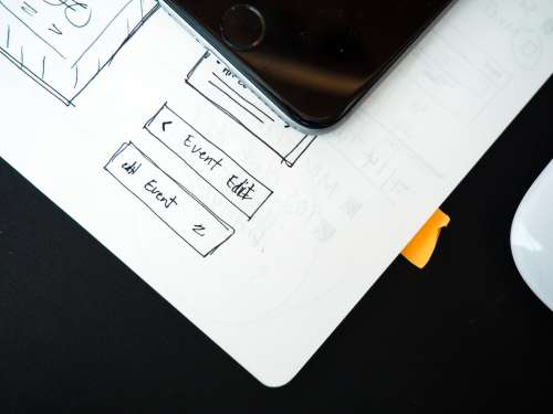 Notebook, Mouse, and Phone on Black Desk