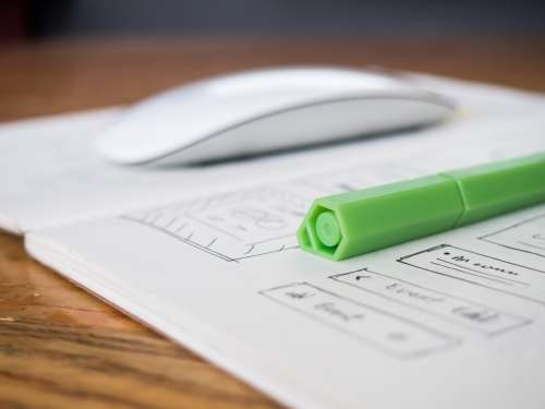 Green Pen and Sketchbook on Desk
