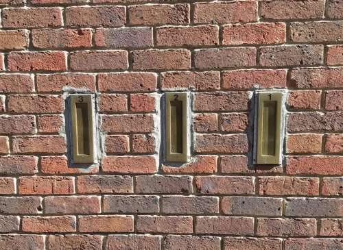 letter boxes three brass brick wall