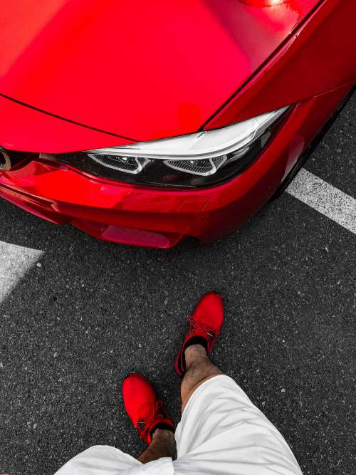 Man in Red Shoes Standing in Front of Ferrari-Red BMW
