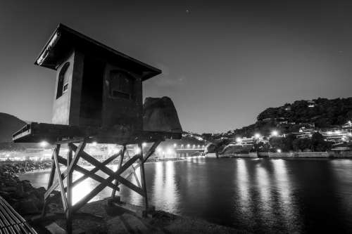 A Battered Hut At The Water's Edge Framed By City Lights Photo