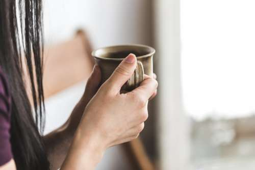 A Close Up Of A Woman Holding A Coffee Cup Photo