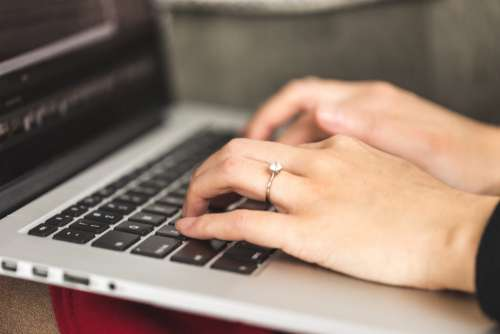 A Close Up Of Hands Typing On A Keyboard Photo
