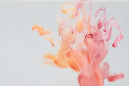 A Few Drops Of Pink And Yellow Trail Colour In Water Photo
