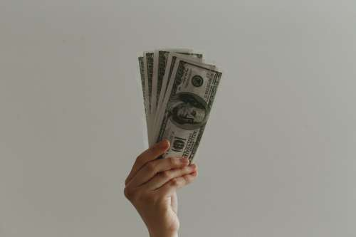 A Hand Holds Up Some Bank Notes Photo