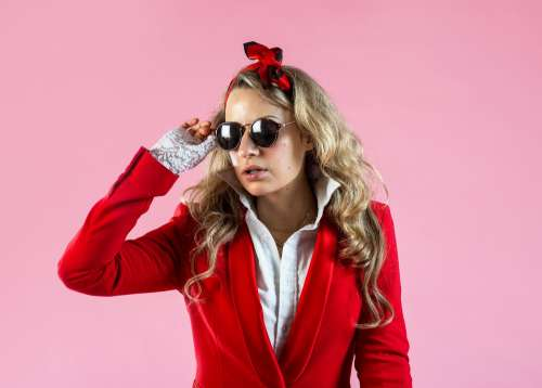 A Model In Red Suit Jacket Removing Sunglasses Photo