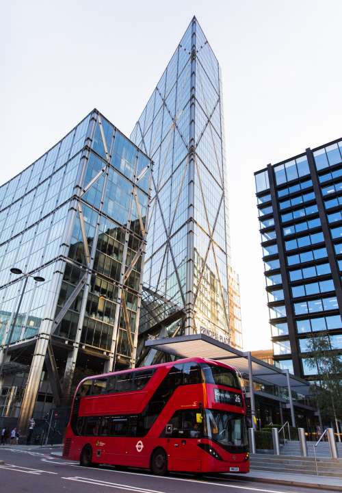 A Red Bus Drives Under Glassy Skyscrapers Photo