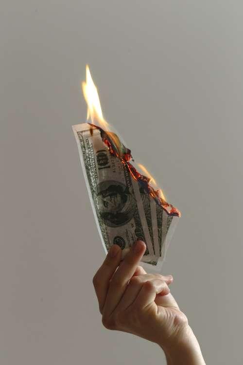 A Single Hand Holding Up Burning Notes Photo