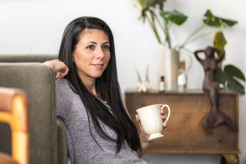 A Young Woman Leans Back On A Couch With A Coffee Photo