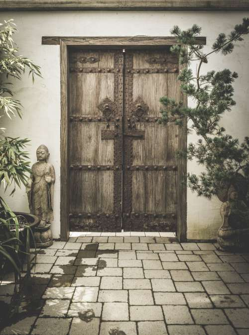 Carved Stone Buddhas Adorn Ornate Wooden Doorway Photo