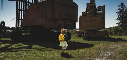 Child Walks Surrounded By Machinery Photo