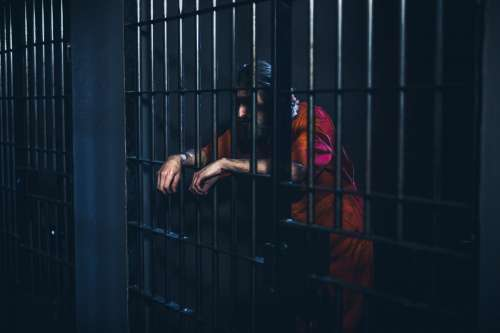 Crestfallen Prisoner Leans On Cell Door Photo