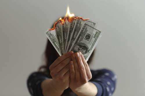 Hands Holding Money Aflame Photo