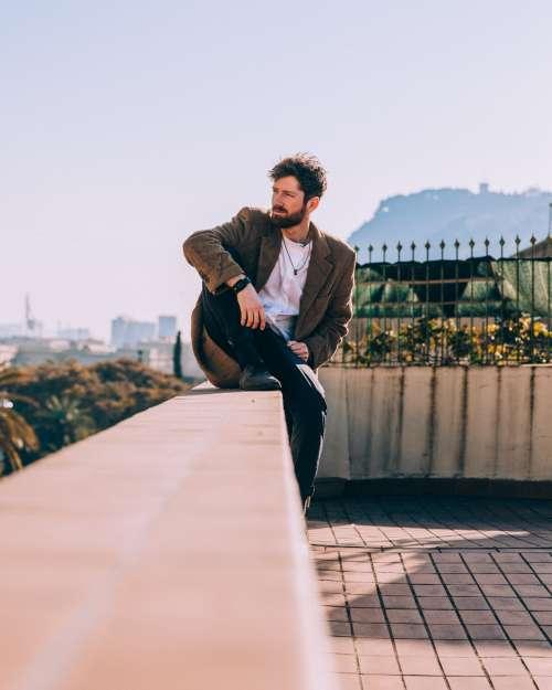 Man Sitting Comfortably On Roof Ledge Photo