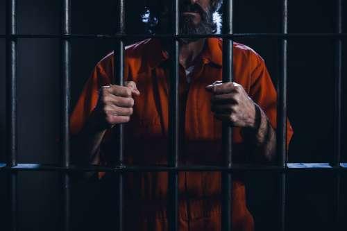 Prisoner Grips Cell Bars Photo