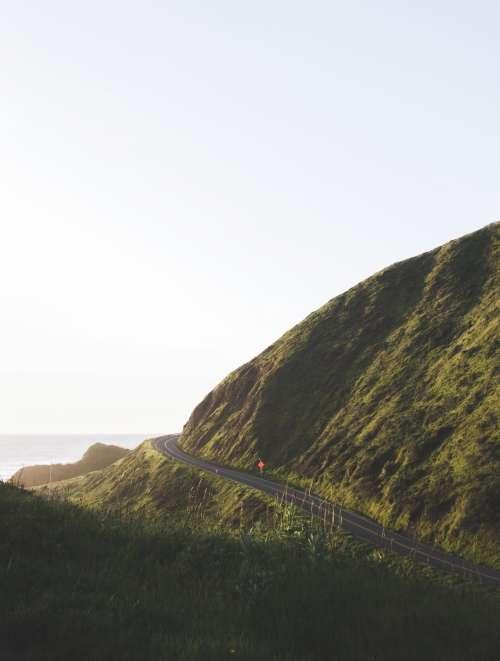Solitary Highway Curves Around Lush Green Hillside Photo