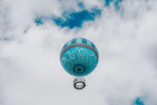 Teal Hot Air Balloon Framed By Puffy White Clouds and Blue Sky Photo