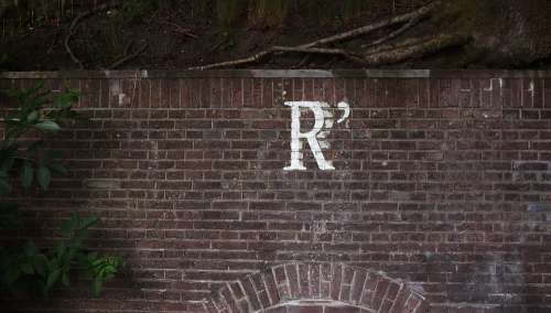 r letter brick wall urban