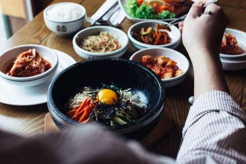 Eating Korean Bibimbap with chopsticks