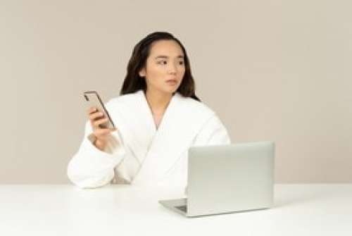 Young Asian Woman Using Phone And Doing Online Shopping