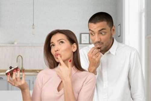 Young Man Looking How Girl Eating Cake And Licking Finger