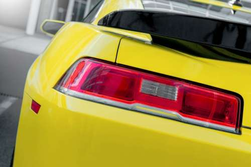 Rear light of yellow luxury car. Close up