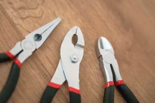 Set of pliers tools on wooden board