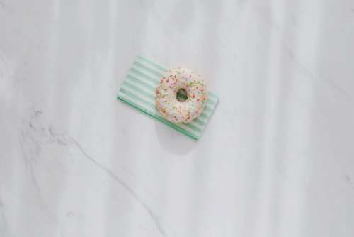 Donuts on paper napkins placed on white marble