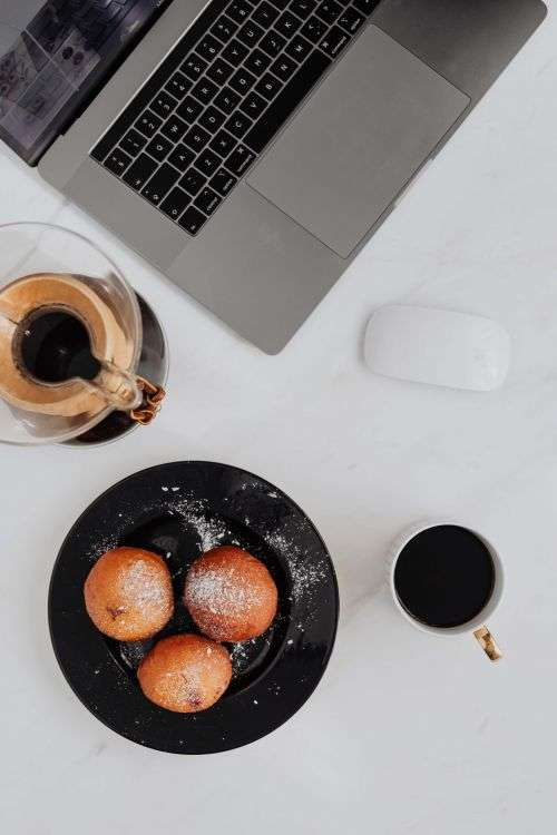 Marble desk with laptop, homemade Polish doughnuts and coffee