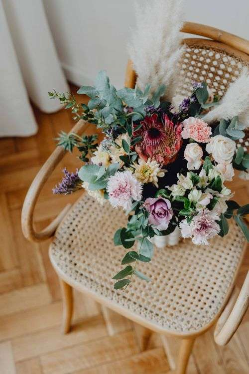 Beautiful bouquet of flowers on a wooden chair