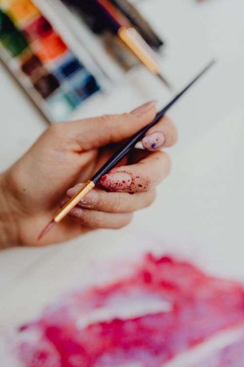 A woman paints with watercolors