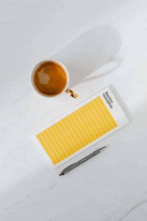 Top view of a marble desk with coffee, notebooks and pen