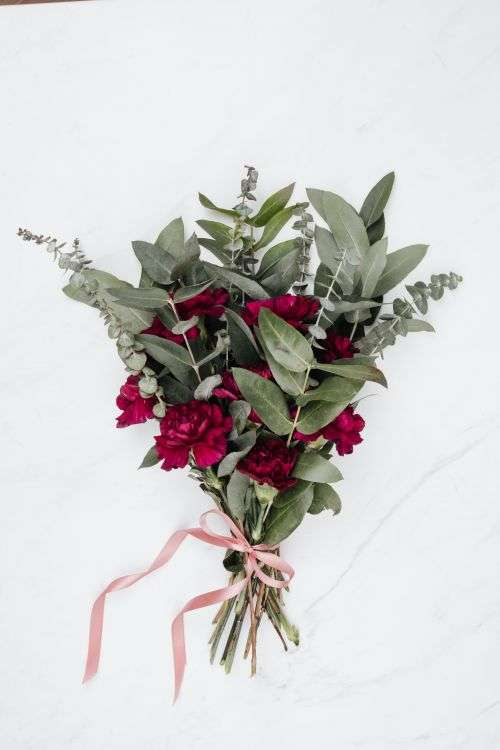 A bouquet of flowers and a red heart-shaped pralines on white marble