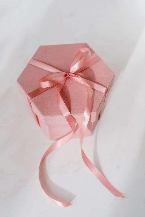 Light pink velvety box with satin ribbon on white marble