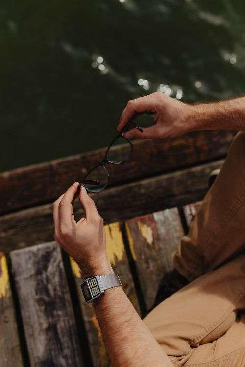 Closeup of glasses & vinatage watch on wrist of man